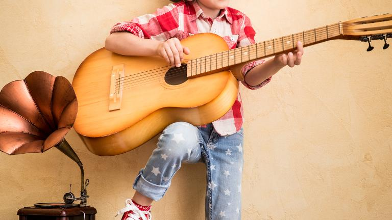 Kid listen music at home. Hipster child with retro vintage acoustic guitar