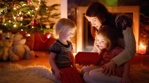 mother and her two little daughters opening a magical Christmas gift